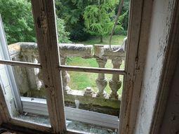 Fenêtre du deuxième étage sans vitre et balcon endommagé.